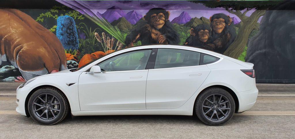 Hvid Tesla Model 3 foran grafittigalleri i Københavns Sydhavn